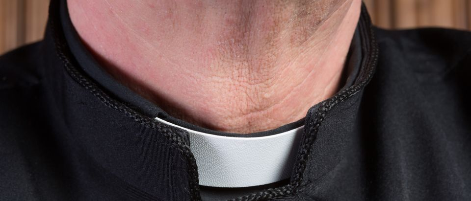 Closeup of the neck of a priest wearing a black shirt with cassock and white clerical collar. (Shutterstock)