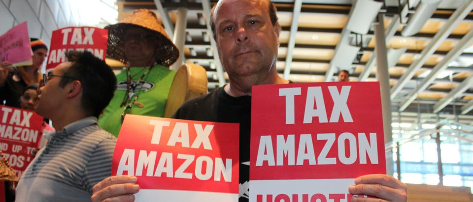 """Protesters hold placards during a city council vote for a new """"head tax"""" on the city's biggest companies, including Amazon.com, as a way of fighting a housing crisis sporsors attibute largely to a local econonimic boom driving real estate costs, in Seattle, Washington, U.S., May 14, 2018. REUTERS/Gregory Scruggs 
