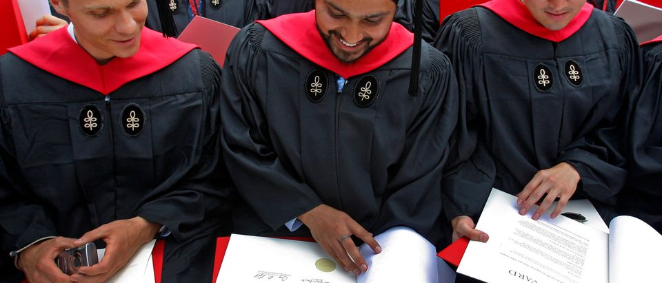 Students look at their diplomas at Harvard Business School's graduation ceremonies in Boston