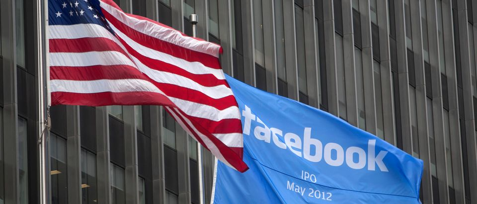 A flag announcing the IPO of Facebook flies next to the American flag outside the offices of J.P. Morgan in New York City