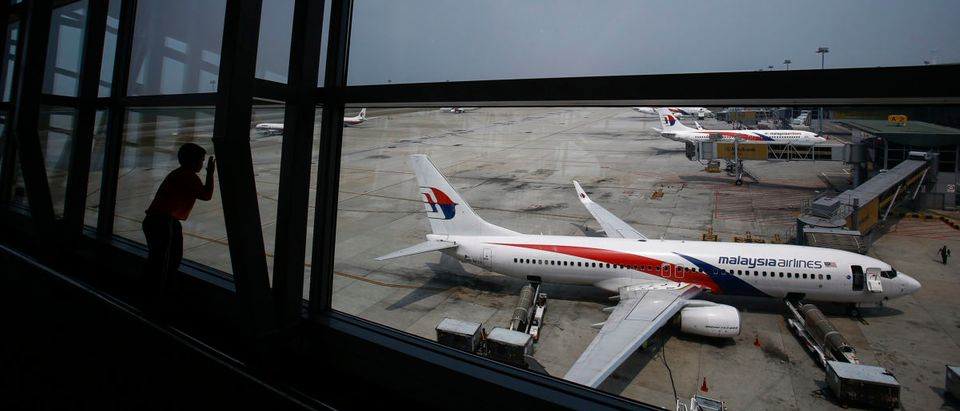 Boy looks at a Malaysia Airlines Boeing 737-800 aircraft on the tarmac at Kuala Lumpur International Airport in Sepang