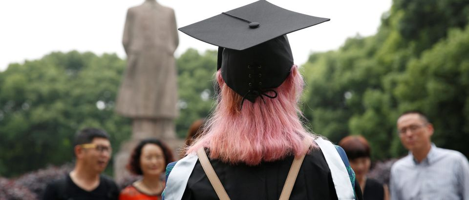 A student stands in front of the statue of Chinese leader Mao Zedong after her graduation ceremony at Fudan University in Shanghai