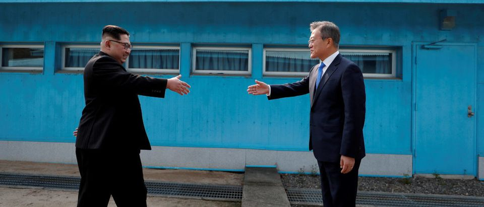 FILE PHOTO: South Korean President Moon Jae-in and North Korean leader Kim Jong Un about to shake hands for the first time at the truce village of Panmunjom