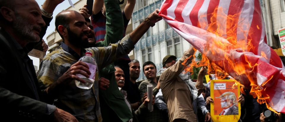Iranians burn a U.S. flag during a protest against President Donald Trump's decision to walk out of a 2015 nuclear deal, in Tehran