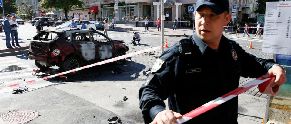Police officer blocks off site where journalist Sheremet was killed by car bomb in Kiev
