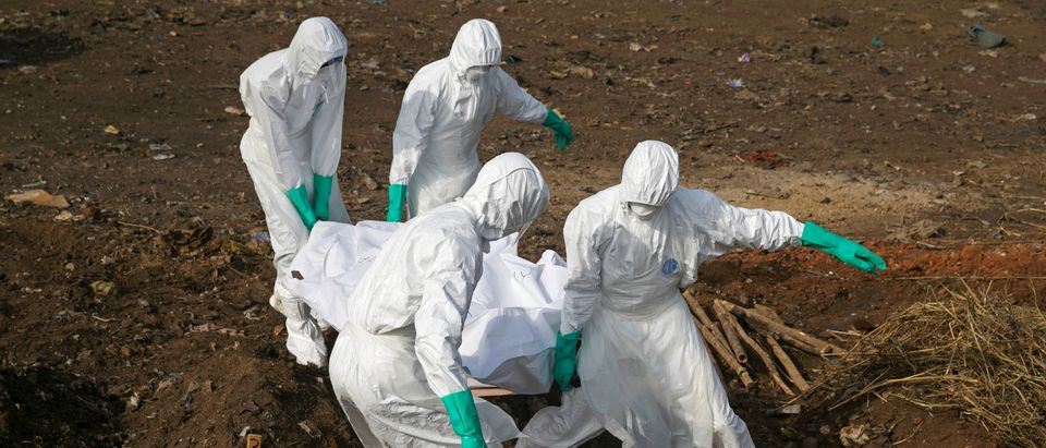 Health workers carry the body of a suspected Ebola victim for burial at a cemetery in Freetown