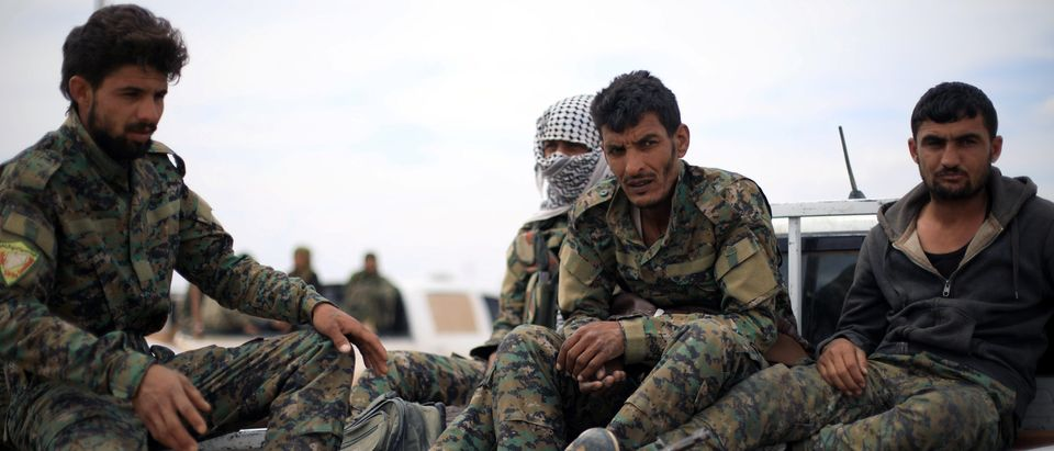 Fighters of Syrian Democratic Forces (SDF) sit at the back of a truck in Deir al-Zor