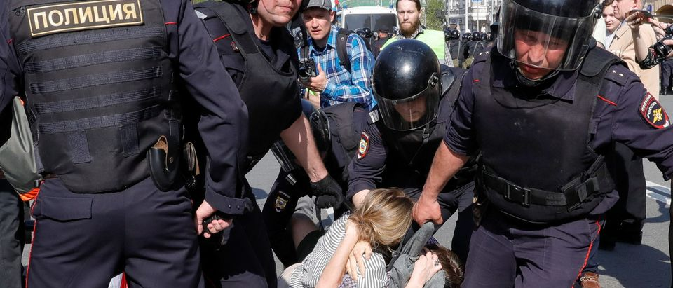 Policemen detain opposition supporters during a protest ahead of President Vladimir Putin's inauguration ceremony, Moscow