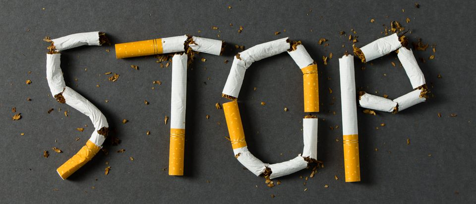 The word stop spelled using cigarettes on black background. (Shutterstock)