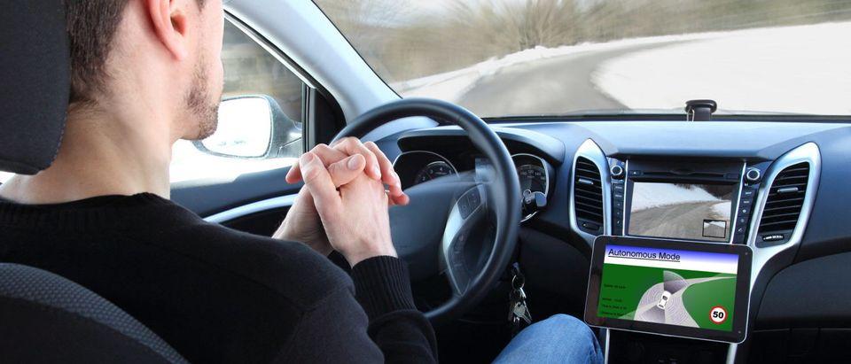 A man is operating, but not manually driving an autonomous vehicle. [Shutterstock - riopatuca]