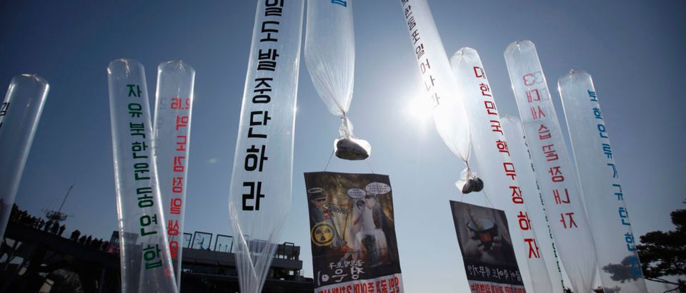 North Korean defectors living in South Korea hold balloons containing leaflets and CDs denouncing North's leader Kim Jong-un, near the DMZ