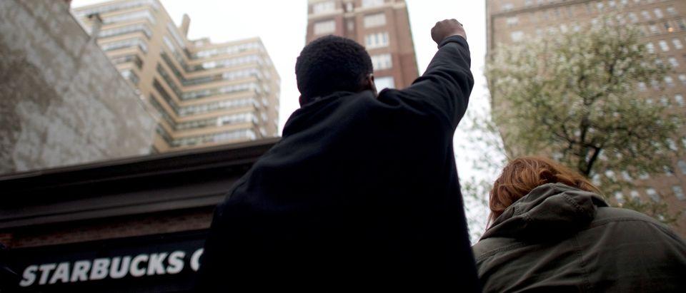 A man raises his arm in protest outside the Center City Starbucks, where two black men were arrested, in Philadelphia, April 16, 2018. REUTERS/Mark Makela