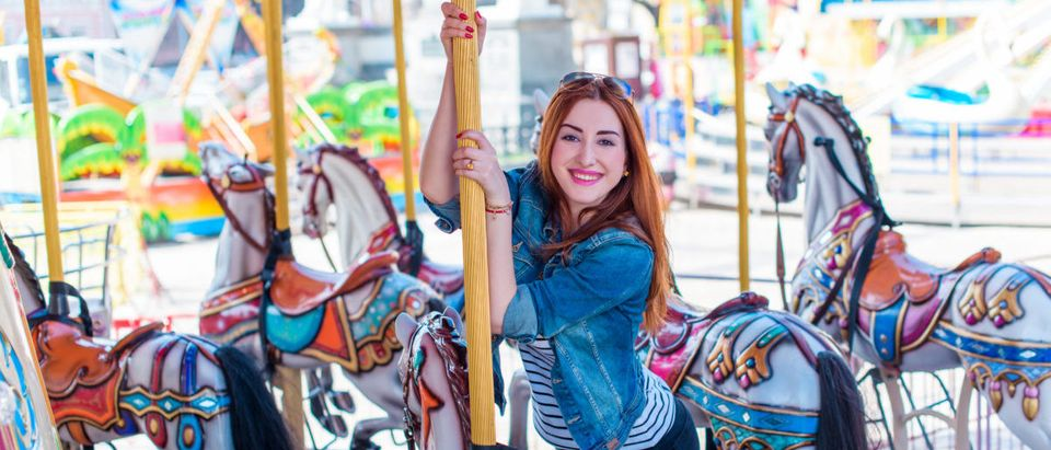An adult girl has fun on the carousel and has a good time. Shutterstock/ T.Den