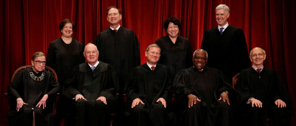 U.S. Chief Justice John Roberts (seated C) leads Justice Ruth Bader Ginsburg (front row, L-R), Justice Anthony Kennedy, Justice Clarence Thomas, Justice Stephen Breyer, Justice Elena Kagan (back row, L-R), Justice Samuel Alito, Justice Sonia Sotomayor, and Associate Justice Neil Gorsuch in taking a new family photo including Gorsuch, their most recent addition, at the Supreme Court building in Washington, D.C., U.S., June 1, 2017. REUTERS/Jonathan Ernst | How To Guess SCOTUS Opinion Assignments