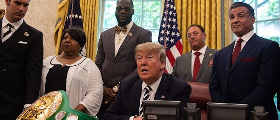 U.S. President Donald Trump speaks before signing a posthumous pardon for former world champion boxer Jack Johnson in the Oval Office at the White House in Washington, DC, on May 24, 2018, joined by boxer Lennox Lewis and actor Sylvester Stallone(R) as he announced the decision. (Photo by NICHOLAS KAMM / AFP) (Photo credit should read NICHOLAS KAMM/AFP/Getty Images)