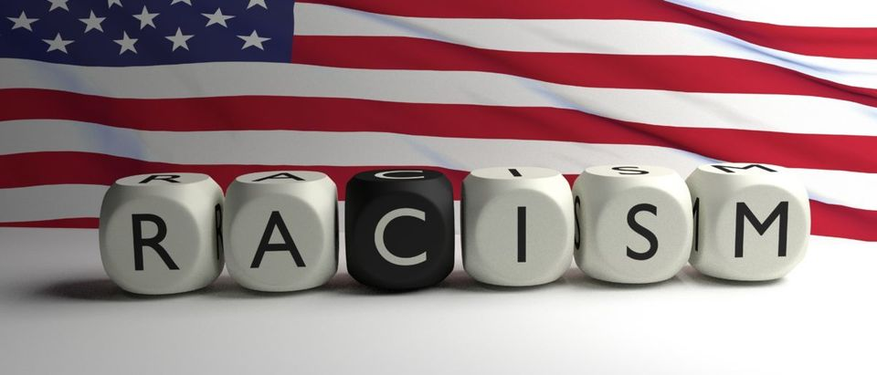 Word RACISM written on dices with flag of United States of America in background. Racism in the USA. 3D render - ShutterStock -- Nikola93