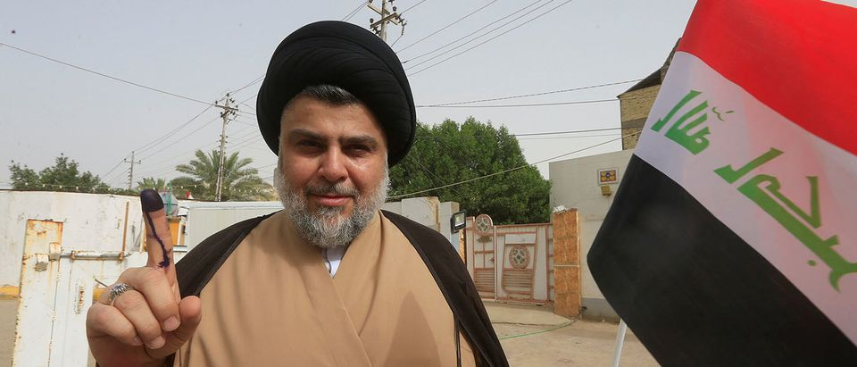 Iraqi Shi'ite cleric Moqtada al-Sadr shows his ink-stained finger after casting his vote at a polling station during the parliamentary election in Najaf