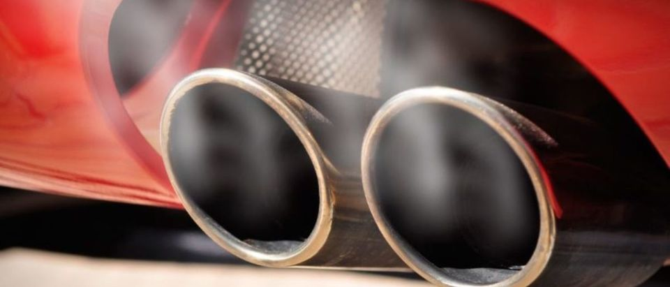 Close up of a red car dual exhaust pipe with smoke around it   Trump Dings Another Emission Rule
