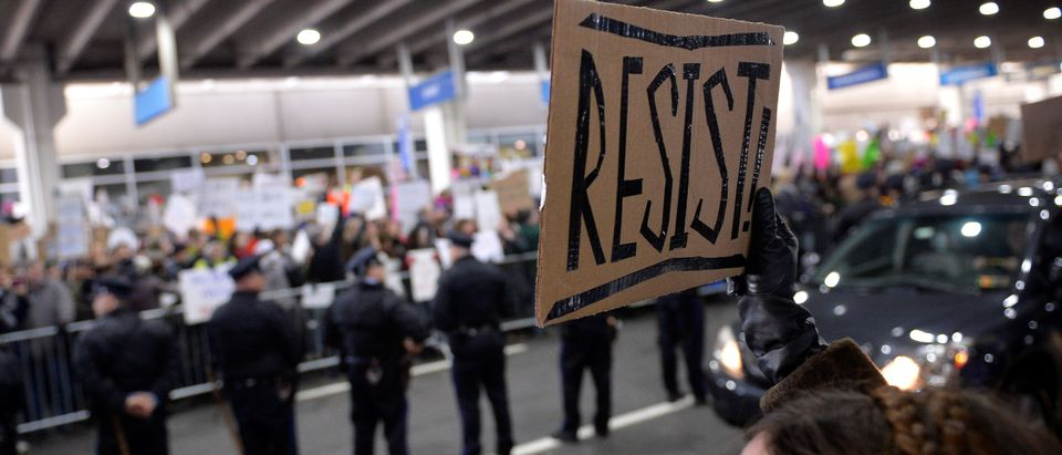 "A demonstrator holds a ""resist"" sign during anti-Donald Trump travel ban protests outside Philadelphia International Airport in Philadelphia, Pennsylvania, U.S., January 29, 2017. REUTERS/Charles Mostoller - RC1C22B44C50"