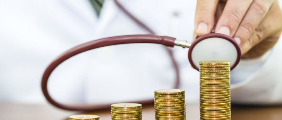 Doctor hand holding stethoscope checking stack of money coins arranged as a graph on wooden table, concept of financial health check and medical expenses (Shutterstock)