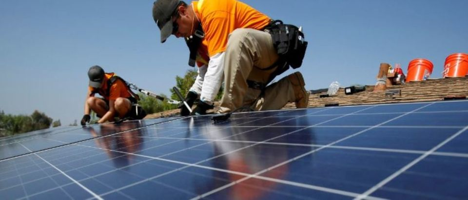 FILE PHOTO: Solar technicians install solar panels on the roof of a house in Mission Viejo, California, U.S. October 25, 2013. REUTERS/Mario Anzuoni/File Photo | Solar Jobs Dropped As Coal Plugs Along