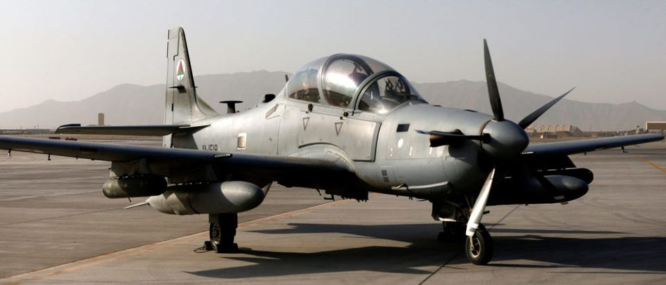 A Blackhawk helicopter flies above a parked A-29 Super Tucano aircraft, during a handover ceremony of Blackhawk helicopters from U.S. to the Afghan forces, at the Kandahar Air base