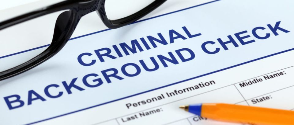 Criminal background check application form with glasses and ballpoint pen. (Shutterstock/Ekaterina_Minaeva)