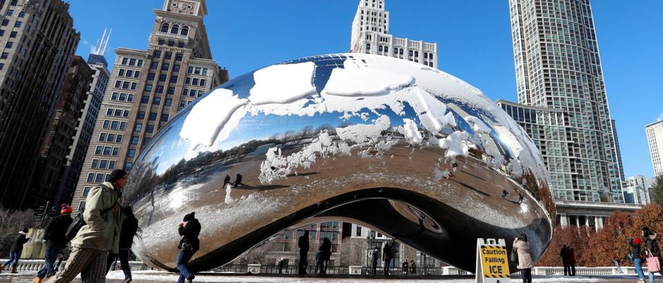 People walk by the snow-covered Cloud Gate sculpture in Chicago