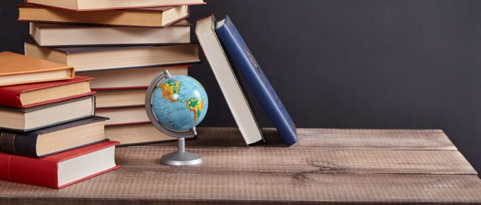Books and a globe perch on a classroom desk. (Shutterstock/Happy Author)