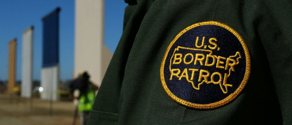 A border patrol officer stands next to some of U.S. President Donald Trump's eight border wall prototypes as they near completion along U.S.- Mexico border in San Diego, California, U.S., October 23, 2017. REUTERS/Mike Blake
