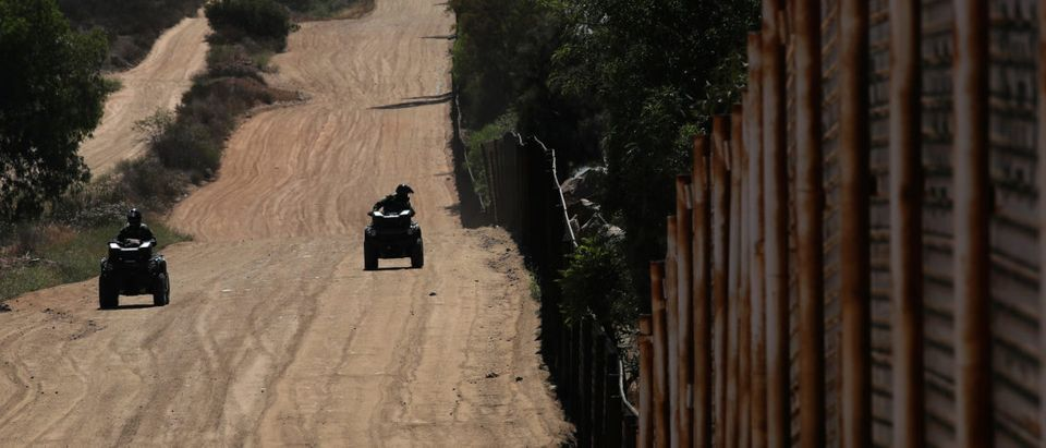 Border patrol agents guard the wall on the U.S. border with Mexico in Tecate, California