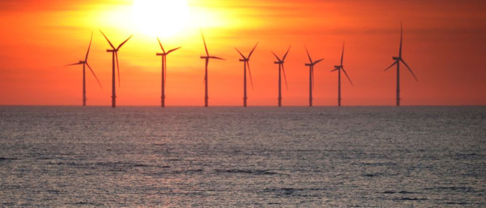 A man stands on the beach as the sun sets behind the Burbo Bank wind farm near New Brighton.