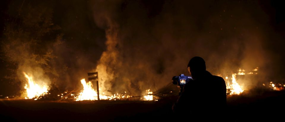 A photographer takes photographs of flames at the Jerusalem Fire in Lake County