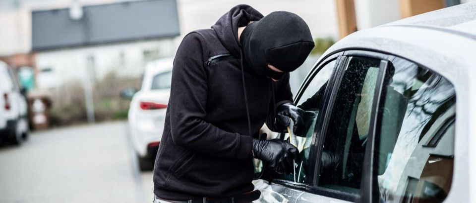 Car thief trying to break into a car with a screwdriver. Car thief, car theft. (Shutterstock/plantic)