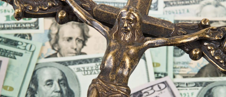 Catholic Crucifix And Money (Shutterstock/