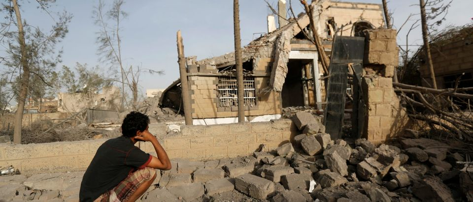 Man sits in front of a house destroyed by air strikes in Sanaa, Yemen