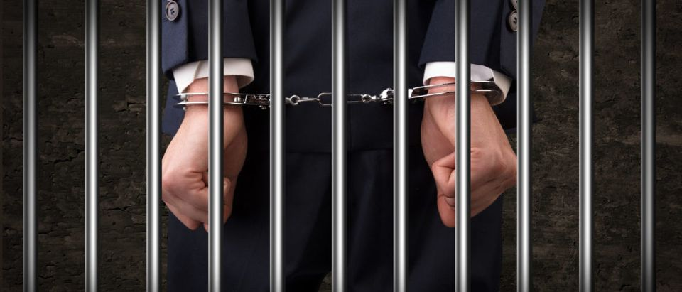 Pictured is a man with handcuffs. ShutterStock - Ra2studio