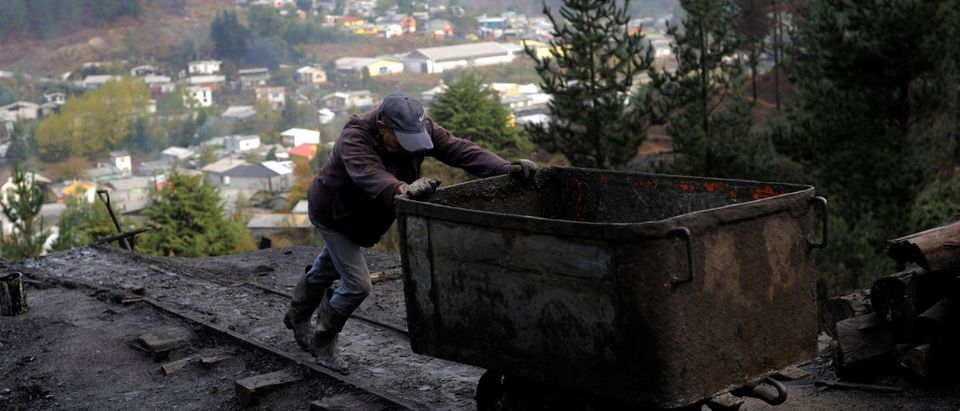 """A coal miner pushes a cart used to transport coal from inside an old artisanal coal mine, so called """"Pique"""", in Curanilahue"""