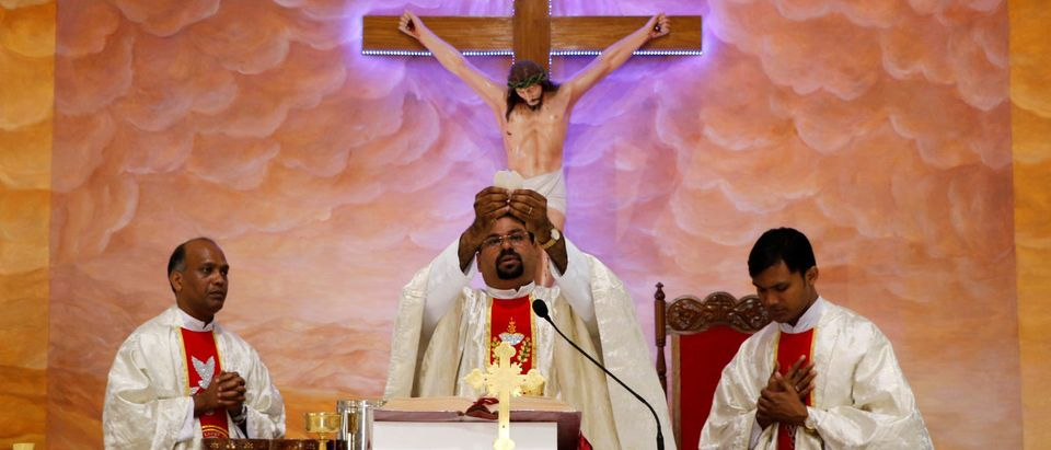 A Christian priest performs Holy Communion as he leads the Easter mass in Agartala