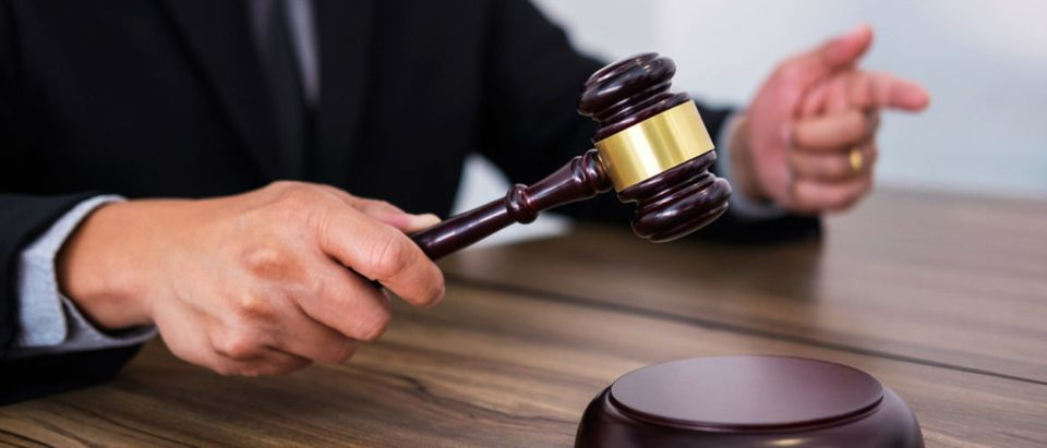 A lawyer or judge hand's strikes the gavel on a sounding block. (Shutterstock/Freedomz)