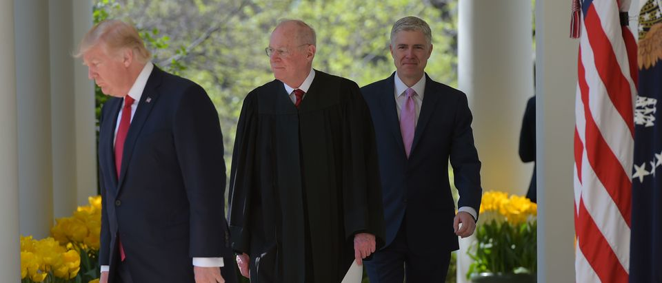 US President Donald Trump arrives with Justice Anthony Kennedy(C) and Neil Gorsuch(R) before Justice Kennedy administers the oath of office as an associate justice of the US Supreme Court in the Rose Garden of the White House on April 10, 2017 in Washington, DC. / AFP PHOTO / Mandel NGAN (Photo credit should read MANDEL NGAN/AFP/Getty Images)