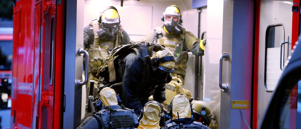 """TOPSHOT - Picture taken on June 12, 2018 shows police officers of a special unit wearing protective clothes and respiratory masks during an operation in Cologne's Chorweiler district, western Germany, where police found toxic substances after storming a flat. - A Tunisian man arrested in Germany is suspected of trying to build a biological weapon using the deadly poison ricin, prosecutors said on June 14, 2018, stressing however there was no indication of any """"concrete attack plans"""". (Photo by David Young / dpa / AFP) / Germany OUT (Photo credit should read DAVID YOUNG/AFP/Getty Images)"""
