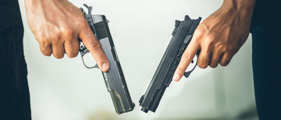 Two people holding a gun at building. Low key photo and selective focus. criminality concept. (Shutterstock/Chayantom Tongmorn)