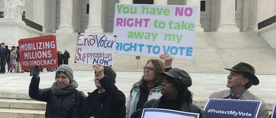 Activists rally ahead of arguments in a key voting rights case at the U.S. Supreme Court in Washington