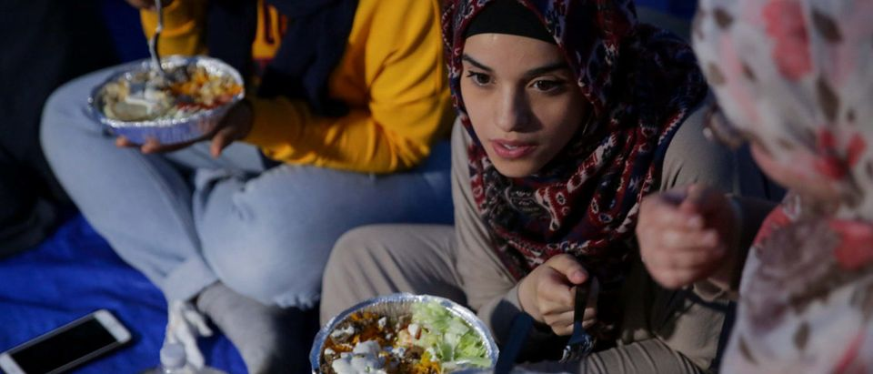 """Muslim women share a meal during an immigration rally and Iftar """"breaking fast"""" during the month of Ramadan outside ICE's New York field office at Foley Square in Manhattan, New York, U.S., May 23, 2018. REUTERS/Amr Alfiky"""