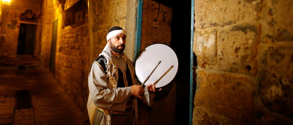 "Michel Ayoub, a Christian Israeli-Arab, holds his drum as he performs the role of ""Musaharati"" during the holy month of Ramadan in the Old City of northern Israeli city of Arce"