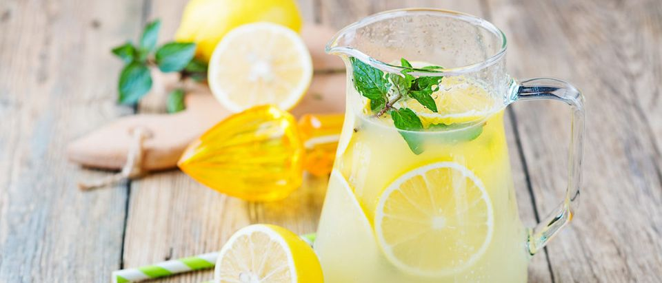Lemonade pitcher with lemon, mint and ice on table -- ShutterStock - Nelea33
