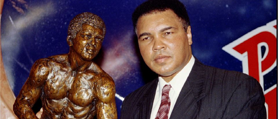 Former heavyweight boxing champion Muhammad Ali stands with a sculpture of himself after it was unveiled in Las Vegas April 21. REUTERS