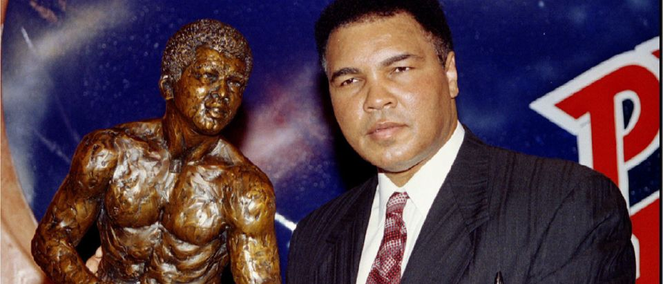 Former heavyweight boxing champion Muhammad Ali stands with a sculpture of himself after it was unve..