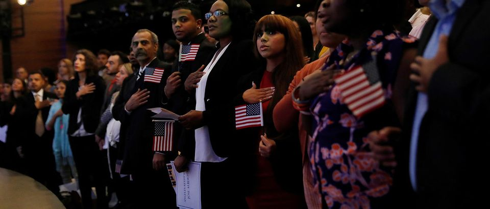 New citizens stand during the National Anthem at a U.S. Citizenship and Immigration Services (USCIS) naturalization ceremony at the New York Historical Society Museum and Library in Manhattan, New York